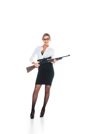 blonde teacher in blous with open neckline, glasses and skirt holding rifle on white background Banque d'images