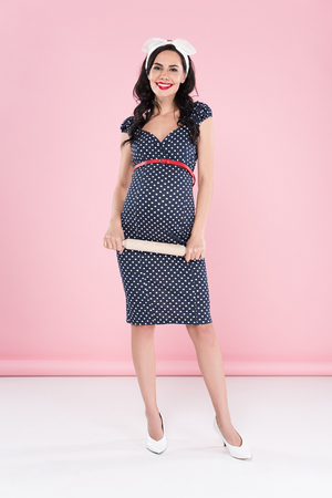 Full length view of pregnant woman in dotted dress holding rolling pin on pink background