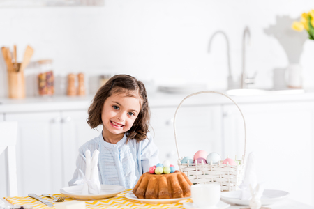 Adorable kid sitting at table with easter cake and painted eggs in kitchen
