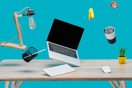 laptop with blank screen and stationery levitating in air at workplace isolated on turquoise Foto de archivo