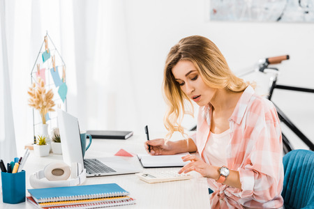 Concentrated woman using calculator and writing in notebook at home office