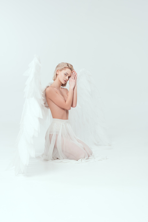 beautiful woman with angel wings looking at camera and posing isolated on white