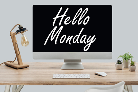 modern workplace with hello monday lettering on computer monitor at wooden desk isolated on grey
