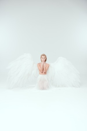 beautiful woman with angel wings doing praying gesture and looking at camera isolated on white Stock Photo