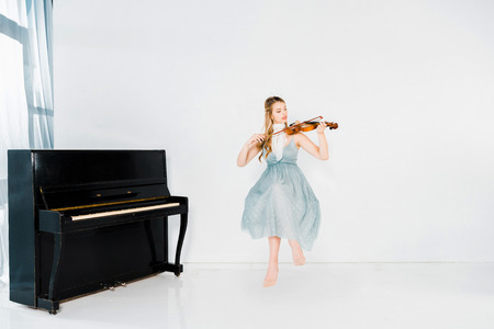 floating girl in blue dress playing violin on white background Banco de Imagens