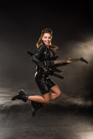 beautiful woman in leather jacket looking at camera and jumping with electric guitar on smoky background