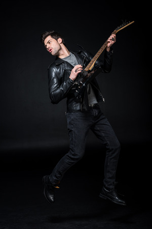 handsome rocker in leather jacket playing electric guitar isolated on black Stock Photo - 119518737