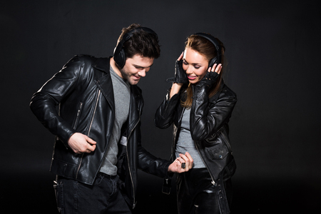 beautiful couple in headphones and leather jackets listening music isolated on black
