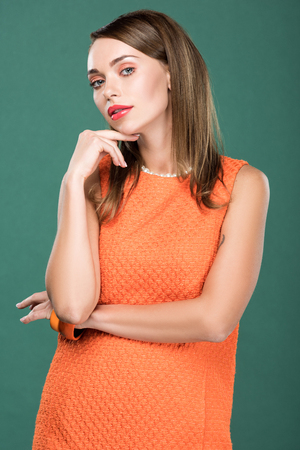 beautiful stylish woman in orange dress touching face and posing isolated on green