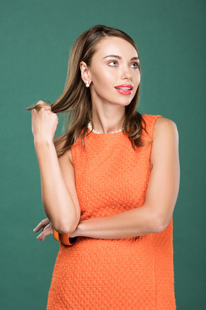 beautiful stylish woman touching hair and posing in orange dress isolated on green