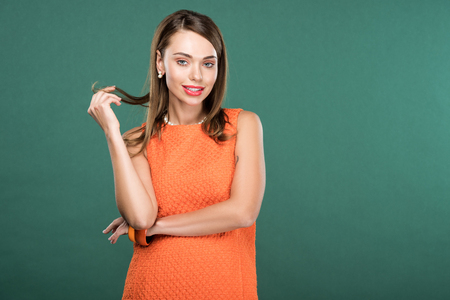 beautiful stylish woman touching hair and posing in orange dress isolated on green with copy space Reklamní fotografie