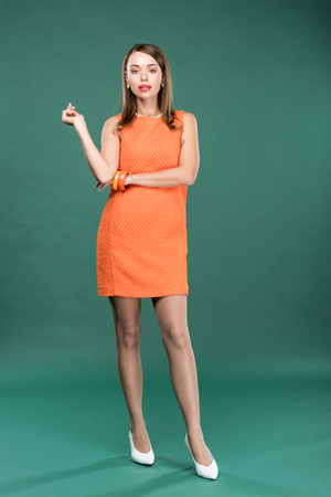 beautiful stylish woman in orange dress looking at camera and posing on green background