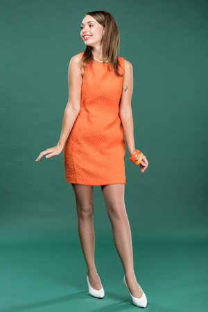beautiful stylish woman in orange dress posing on green background