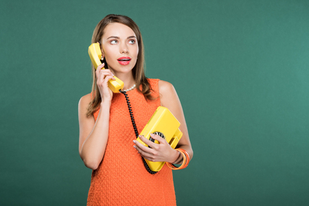 beautiful stylish woman talking on retro telephone isolated on green with copy space