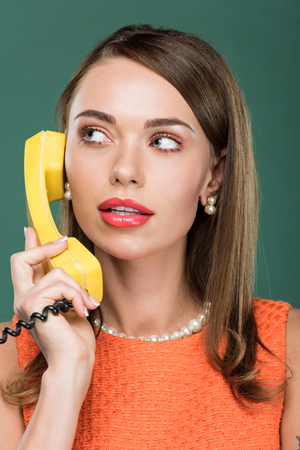 beautiful stylish woman looking away and talking on retro telephone isolated on green