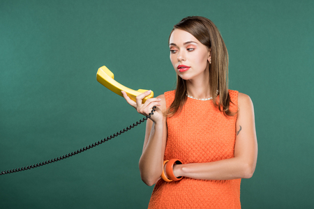 beautiful stylish woman holding retro telephone isolated on green