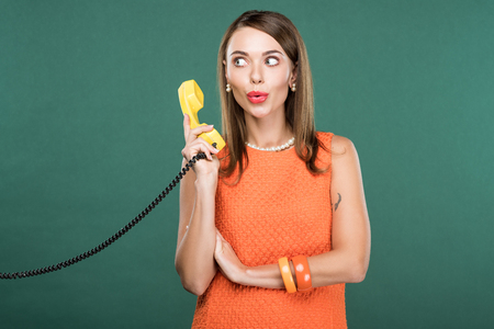 beautiful stylish woman pouting lips and holding retro telephone isolated on green