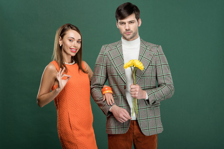 beautiful woman doing ok sign while man in vintage clothes holding flowers isolated on green