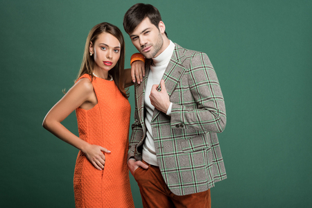 beautiful woman embracing handsome man in vintage clothes isolated on green