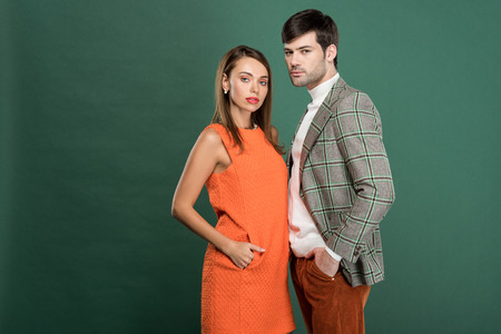beautiful couple in vintage clothes posing and looking at camera isolated on green with copy space Reklamní fotografie
