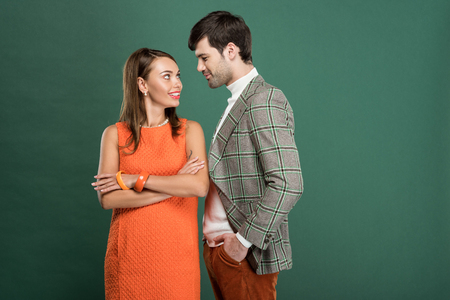 beautiful smiling couple in vintage clothes looking at each other isolated on green