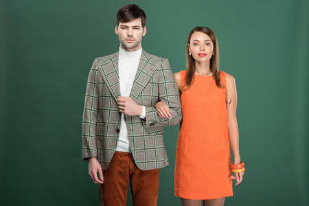 beautiful couple in vintage clothes posing isolated on green