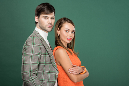 beautiful couple in vintage clothes posing and looking at camera isolated on green with copy space Фото со стока