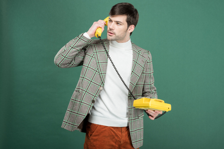 handsome man in vintage clothes talking on retro rotary dial phone isolated on green Reklamní fotografie