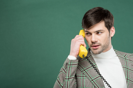 handsome man in vintage clothes talking on retro telephone isolated on green with copy space