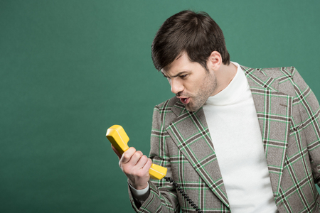 handsome man in vintage clothes shouting at retro telephone isolated on green with copy space
