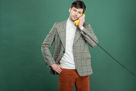handsome man in vintage clothes talking on retro telephone isolated on green