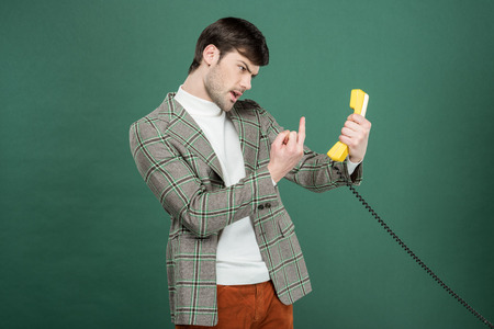 angry handsome man in vintage clothes showing middle finger in front of retro telephone isolated on green