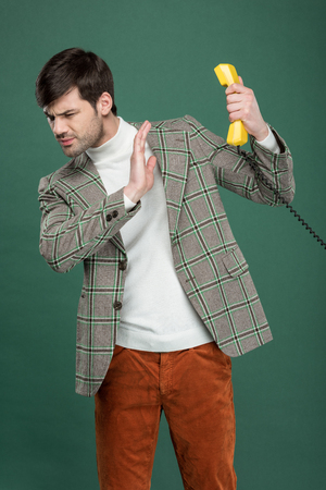 dissatisfied handsome man in vintage clothes refusing phone call and gesturing with hand isolated on green