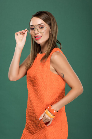 beautiful smiling woman in orange dress and glasses looking at camera and posing isolated on green