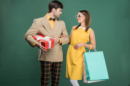 beautiful couple in vintage clothes with shopping bags isolated on green