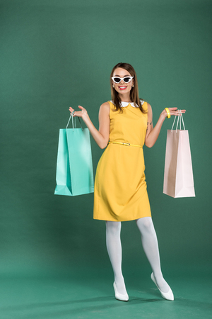 smiling stylish woman in yellow dress and sunglasses with shopping bags posing on green background