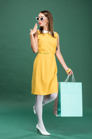stylish woman in yellow dress and sunglasses with shopping bags gesturing with hand on green background