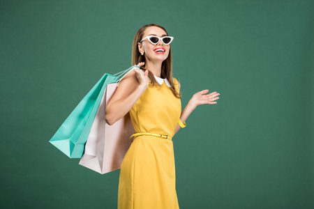 happy stylish woman in yellow dress and sunglasses with shopping bags isolated on green