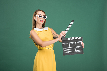 beautiful stylish woman in yellow dress and sunglasses holding film clapperboard isolated on green Stockfoto