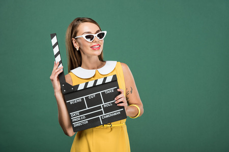 beautiful smiling stylish woman in yellow dress and sunglasses holding film clapperboard isolated on green Reklamní fotografie