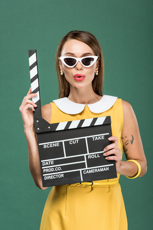 beautiful stylish woman in yellow dress and sunglasses holding film clapperboard isolated on green 版權商用圖片