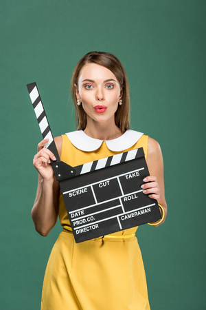 beautiful stylish woman in yellow dress looking at camera, pouting lips and holding film clapperboard isolated on green