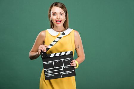 beautiful stylish woman in yellow dress looking at camera and holding film clapperboard isolated on green
