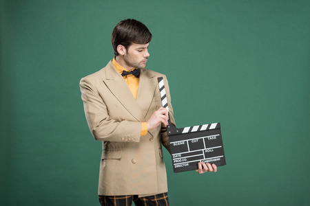 handsome man in vintage clothes holding film clapperboard isolated on green