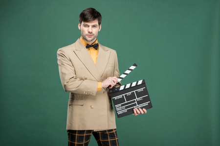 handsome man in vintage clothes looking at camera and holding film clapperboard isolated on green Reklamní fotografie