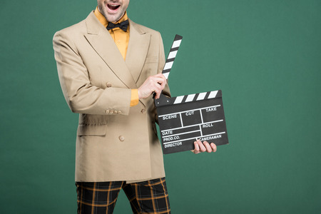 cropped view of excited man in vintage clothes holding film clapperboard isolated on green