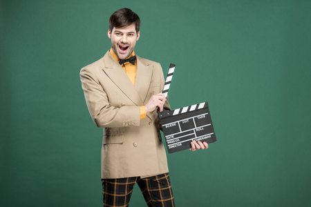 excited handsome man in vintage clothes looking at camera and holding film clapperboard isolated on green