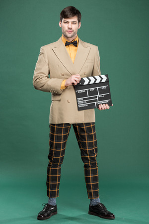 handsome man in vintage clothes looking at camera and holding film clapperboard on green background Reklamní fotografie