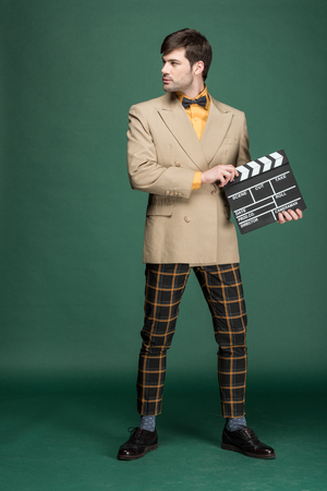 handsome man in vintage clothes holding film clapperboard on green background