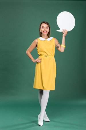 beautiful stylish woman in yellow dress looking at camera and holding speech bubble on green background